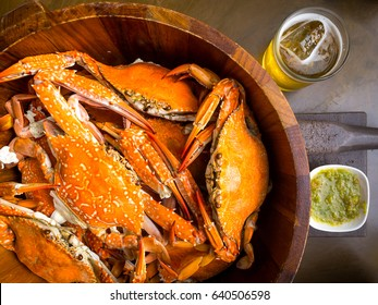 Fresh steamed crab in wooden bucket, spicy sauce and cold beer