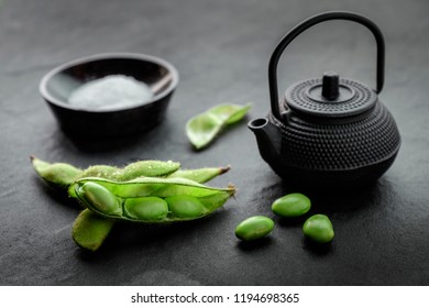 Fresh steamed edamame sprinkled with sea salt on a stone tabletop, Green Japanese Soybean in wooden bowl on table