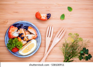 Fresh steamed red crabs leg in bowl . Red crabs leg with ingredients. Steamed red crabs leg with herbs Fennel ,parsley,rosemary,lemon and mint with fork on wooded cutting board.