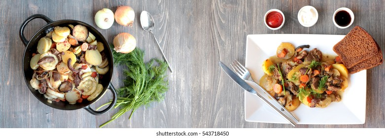 Fresh stew with herbs and sauces on wooden table. Wide panoramic image.