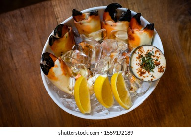 Fresh Stone Crab Claws with lemon and lime, sauce and ice in a dish in a restaurant