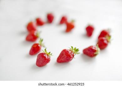 Fresh strawberries array heart shape on table