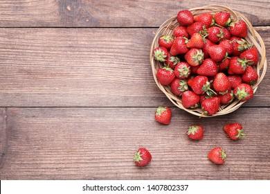 Fresh strawberries in basket on brown wooden table