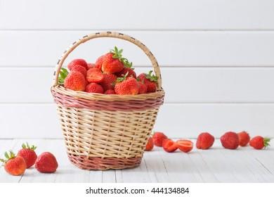 fresh strawberries in basket on white wooden background