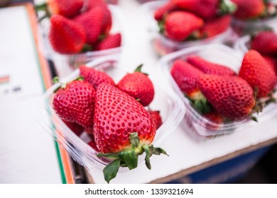 Fresh strawberries in baskets for sale at farmers marketplace