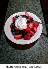 Fresh strawberries, blackberries, and blueberries with cream in a bowl.