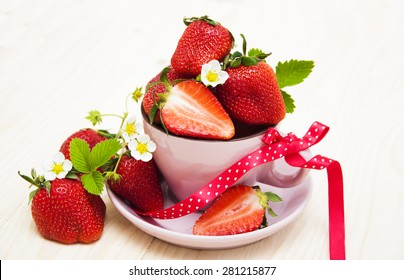 Fresh strawberries with blossom and leaves in a cup on a white wooden background