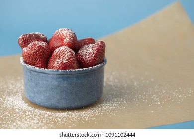Fresh Strawberries in Blue Bowl Sprinkled with Confectioner's Sugar on Parchment Paper and Blue Background