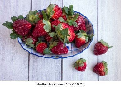 Fresh strawberries in a blue and white oval bowl on a wood surface.  Overhead view.