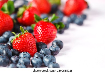 Fresh strawberries and blueberries, copy space