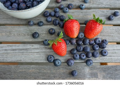 Fresh strawberries and blueberries gray wooden planks. Close- upwith fresh mixed berries. Fruits for a healthy nutrion and lifestyle.