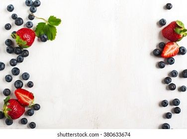 Fresh strawberries and blueberries on wooden background
