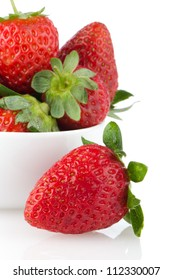 Fresh strawberries in bowl on white reflective background.