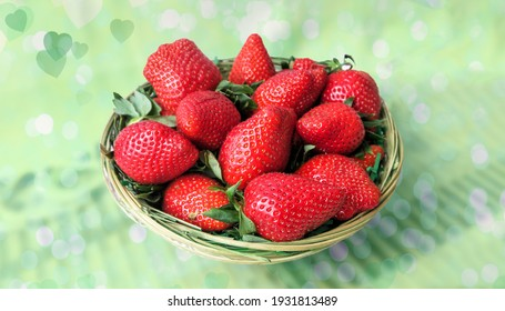 Fresh strawberries in a bowl on a wooden table. A wicker basket with berries on a blurry brown, pink and green background.