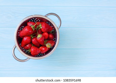 Fresh Strawberries in the Colander on Natural Blue Wood Background. Top View