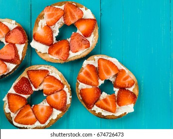 Fresh Strawberries and Cream Cheese On a Bagel Against a Blue Background
