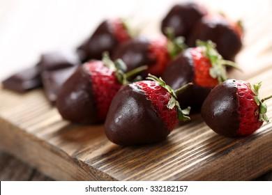 Fresh strawberries dipped in dark chocolate on grey wooden background