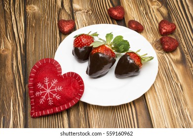 Fresh strawberries dipped in dark chocolate and heart on wooden background. Valentine's Day