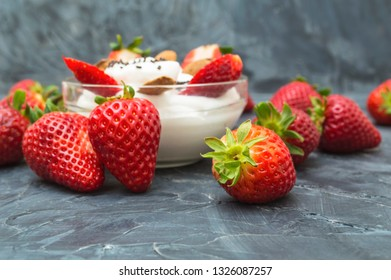 Fresh strawberries fruit with whipped cream on dark background