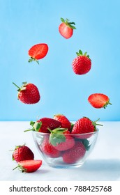 Fresh strawberries in a glass bowl with flying slices on a blue background. toning. selective focus