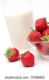 Fresh strawberries and a glass of milk on a white background