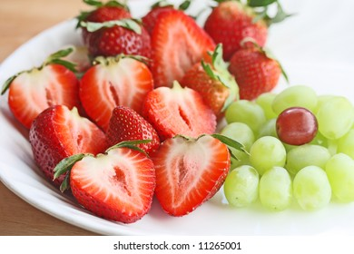 Fresh strawberries and grape on a dish for healthy eating concept