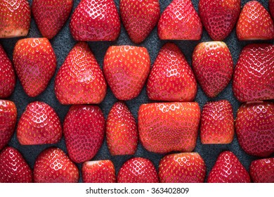 Fresh strawberries halves symetrical background from above