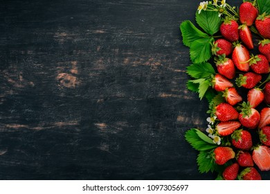 Fresh strawberries. On a black wooden background. Top view. Copy space.