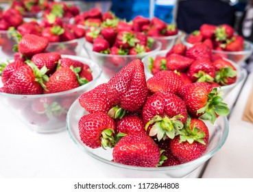 Fresh strawberries on display at a farmers market in New Zealand, NZ - organic spray-free fruit presented in plastic-free glass bowls with shallow depth of field