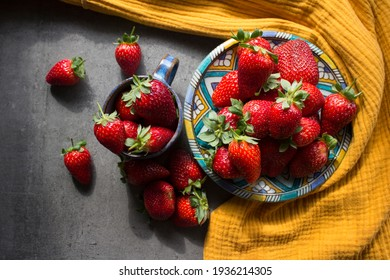 A lot of fresh strawberries on a table. Top view photo of juicy fruits, blue ceramic plate and cup, yellow linen kitchen towel. Healthy eating concept.