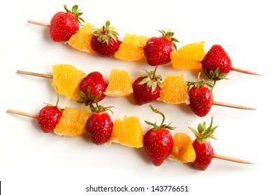 Fresh strawberries and orange slices on skewers