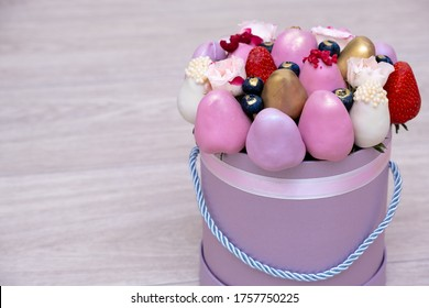 Fresh strawberries in pink, gold and white chocolate with pink flowers in the form of a fruit bouquet. High quality photo