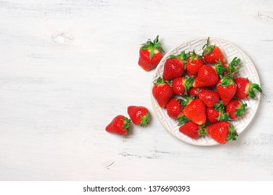 Fresh strawberries in plate on rustic white wood background. Top view.