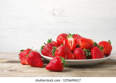 Fresh strawberries in plate on rustic white wood background.