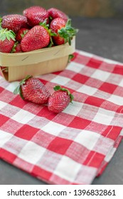 Fresh Strawberries in a Produce Basket with Two Isolated in Front on Red and White Checked Napkin