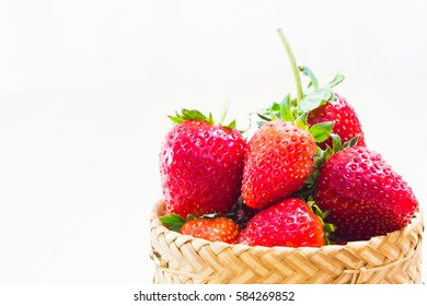 fresh strawberries put the overflow from baskets woven vintage.On white wood background.