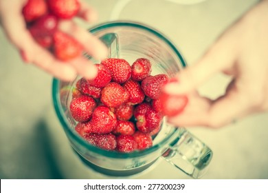 Fresh strawberries putting in blender cup and hands with some berries are blurry. Selective focus. Toned image