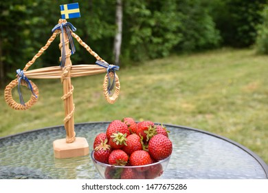 Fresh strawberries and a small maypole outdoors on a table in a garden