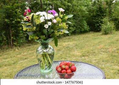 Fresh strawberries and summer flowers on a table in a green garden