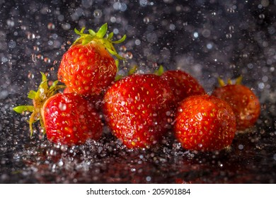 Fresh strawberries with water drops isolated on black background. Soaking in rain.
