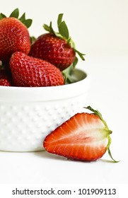 Fresh strawberries in a white bowl on white background