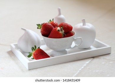 Fresh strawberries in a white porcelain cup among porcelain fruit sculptures: apple, pear and fig on a vintage wooden tray on a stone surface. It can be used for food and cooking magazines