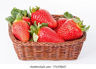 Fresh strawberries in wicker basket close-up on white background