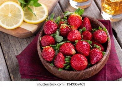 Fresh strawberries in a wooden bowl with dreinks and sliced lemons in background