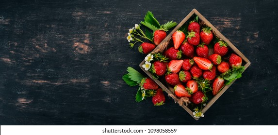 Fresh strawberries in a wooden box. On a wooden background. Top view. Copy space.