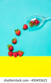 Fresh strawberry in a cup on blue and yellow background. Creative strawberry flat lay.