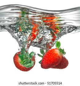 Fresh strawberry dropped into water with splash isolated on white
