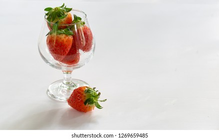 Fresh strawberry in the glass cup on dark white background / Select focus