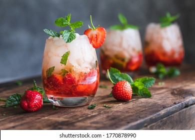 Fresh strawberry mojito drinks. There are three drinks on a vintage wooden dark table.  The cocktails or mocktails are decorated with strawberries and fresh mint. Copy space room for text.
