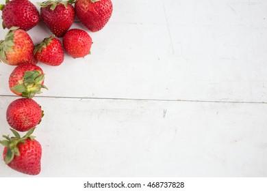 Fresh strawberry on white wooden background.